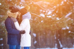 romantic couple hugging in winter forest