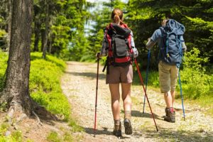 man and woman hikers on forest path