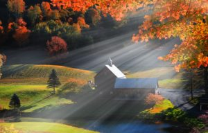 Old barn in Vermont rural side surrounded by fall foliage