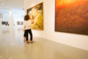 Blurred image of two people admiring paintings at the Brattleboro Museum and Art Center